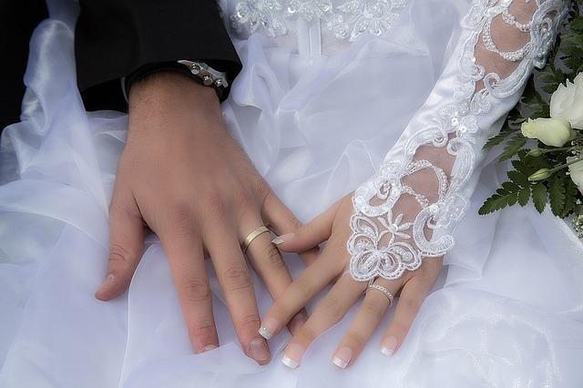 結婚式の二人が手を重ねている
