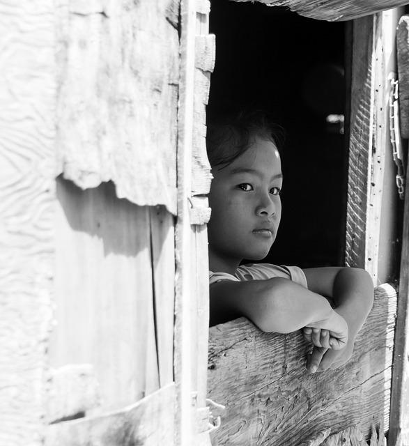 窓から外を見る少女