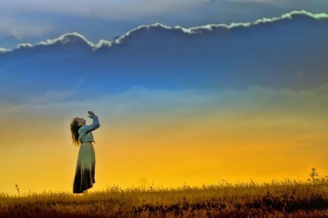 空を見上げて祈る女性