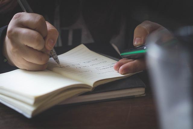 ノートにメモをしている手