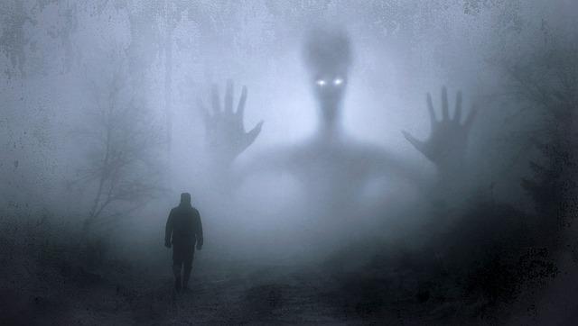 霧の立ちこめる森で歩く男性と待ち受ける大きな影