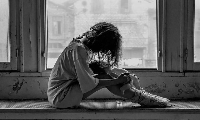 窓際で膝を抱える少女