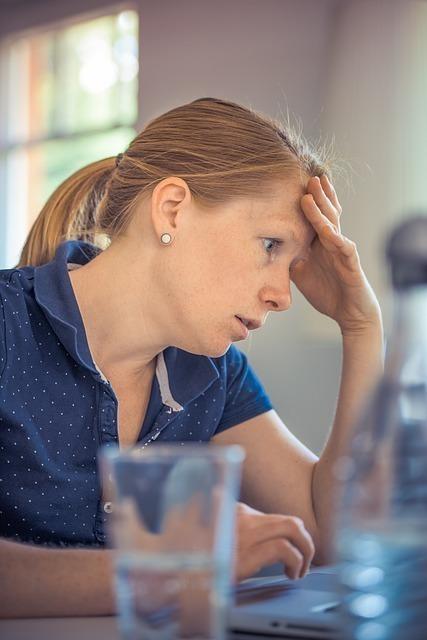 頭を抑えながらパソコンに向かう女性