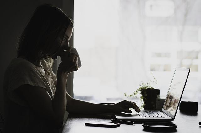 暗い部屋でパソコンに向かう女性