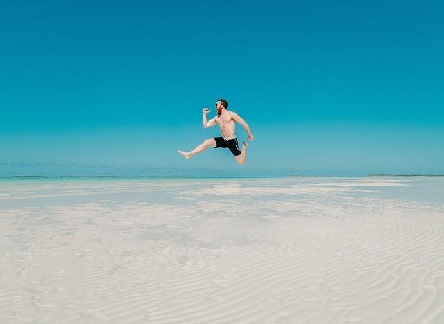 白い砂浜で大きくジャンプする男性