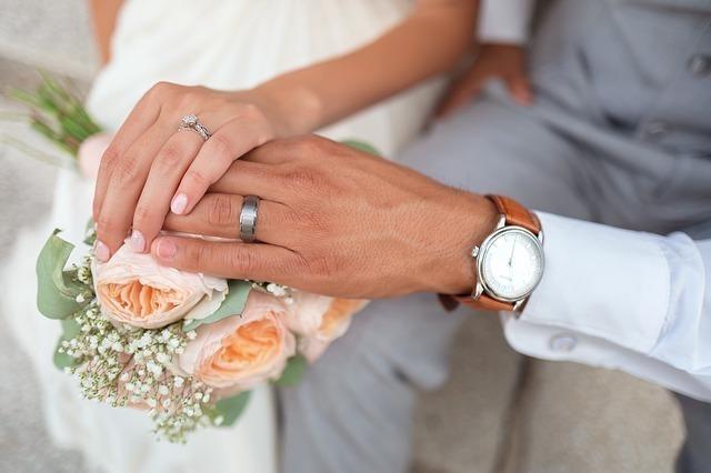 結婚指輪を見せるように重なる男女の手