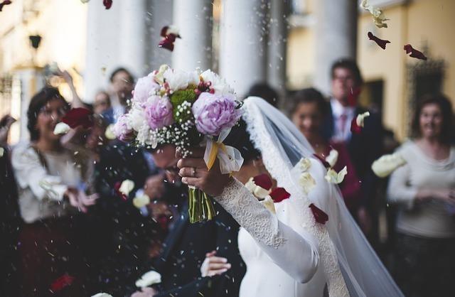 結婚式でライスシャワーを浴びる新婚夫婦