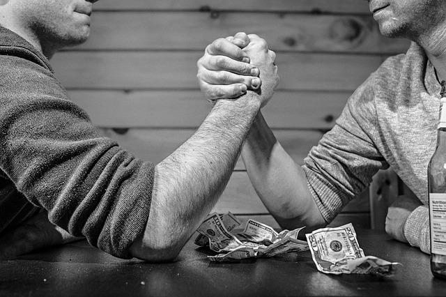 腕相撲する男性と散らばったお金
