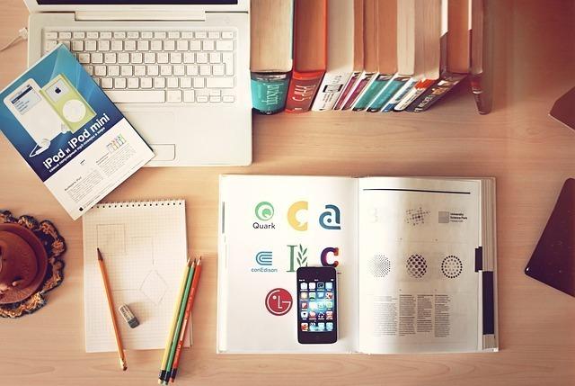 机にデザインの教本や文具とパソコンが広がっている画像
