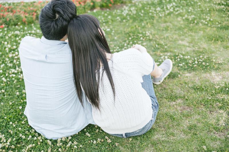 草原に男女が肩を並べて座っている