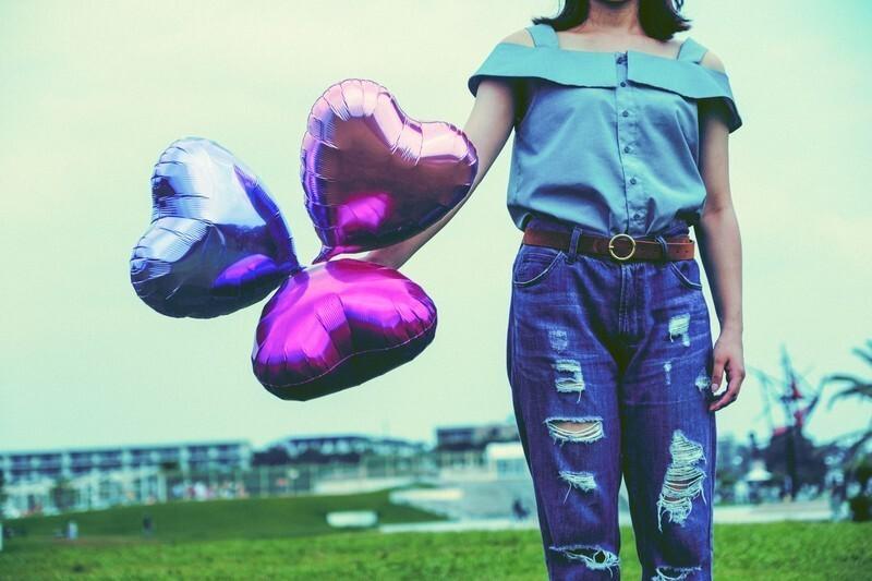 ハート型の風船を持っている女性