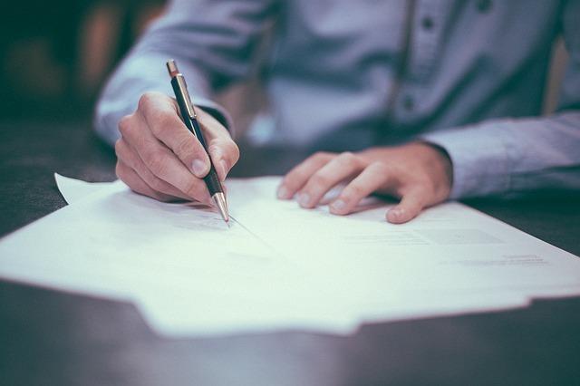 ペンで紙に書く男性
