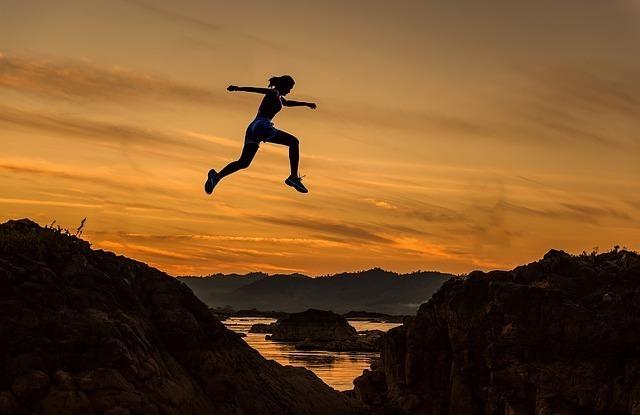 岩から岩へ飛び移ろうとする女性