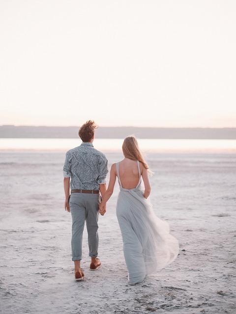 白い砂浜を手をつないで歩くカップル