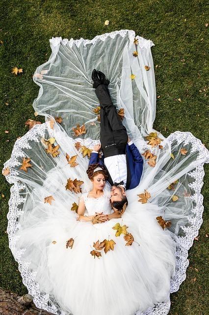 芝生の上に寝転がる新郎と新婦