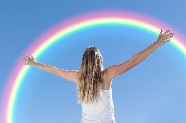 虹を見上げて両手を広げている女性の後ろ姿