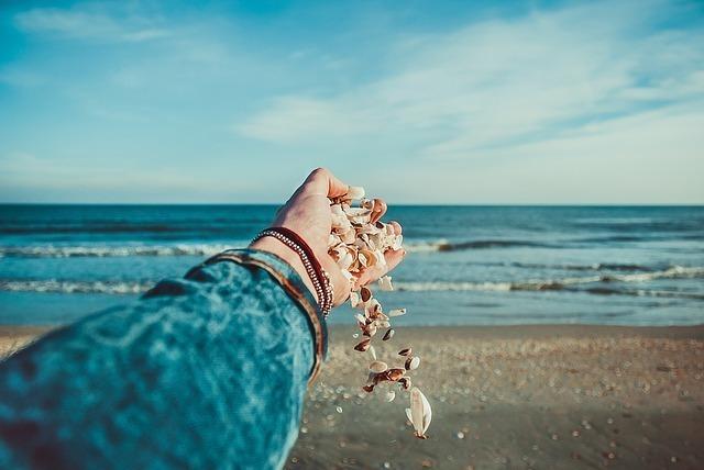 海に向かって差し出した手から貝殻がこぼれ落ちている