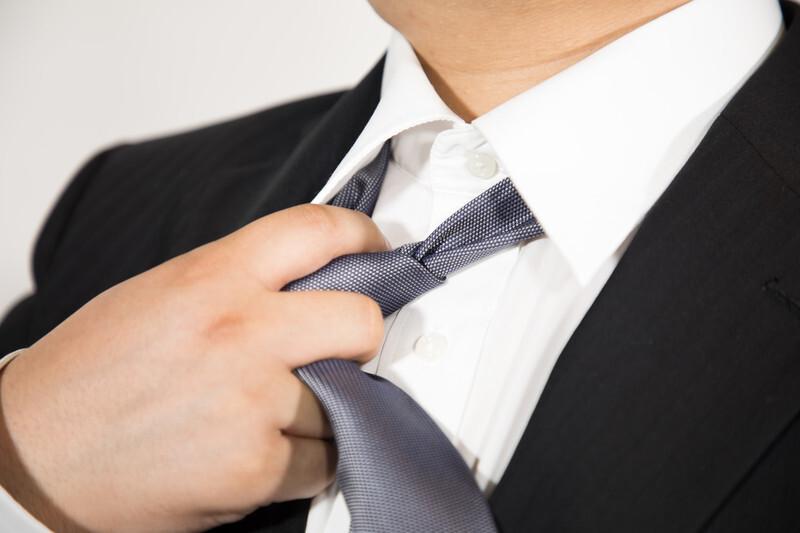ネクタイを緩める手