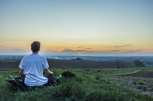 海に向かって瞑想する男性