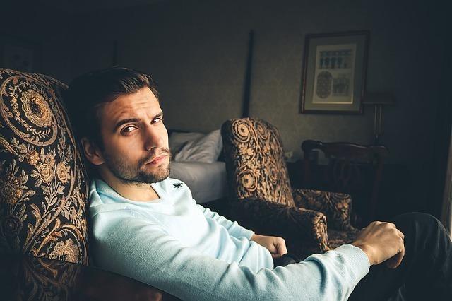 ソファーに座ってこちらを見ている男性
