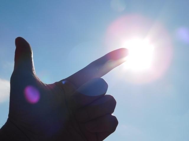 太陽を指差す手