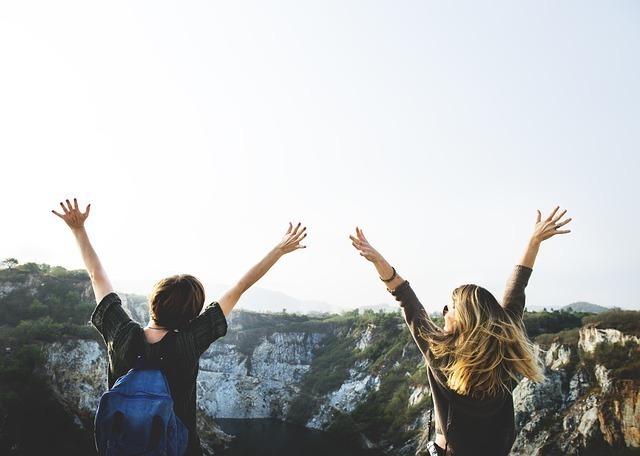山に向かって手を伸ばすカップル
