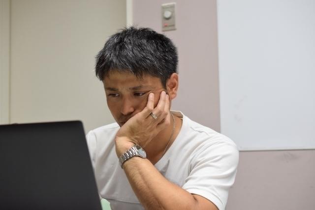 パソコンの前でひじをつく男性