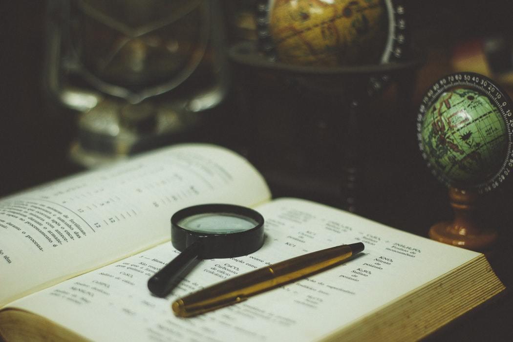 辞書の上に虫メガネとペンが置いてある画像