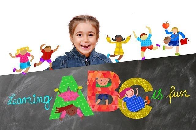 ABCと書かれたボードの後ろに女の子がいる