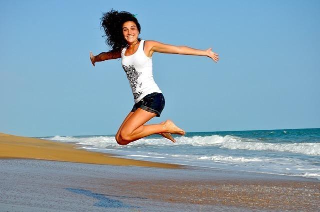 海辺でジャンプをしている女性