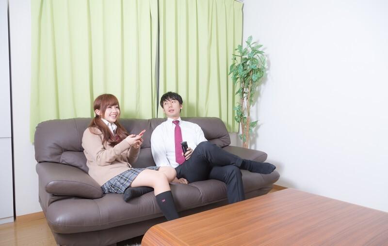 ソファーに座っている女子学生とサラリーマン