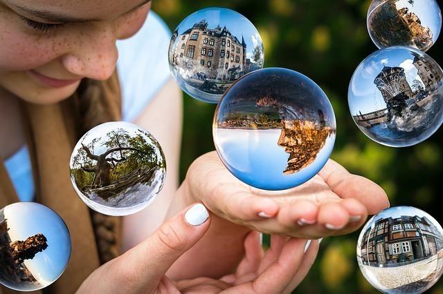 様々な光景が浮かぶ透明な球と女性