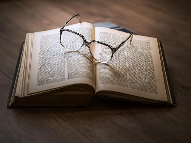 眼鏡が開いた本の上に置かれている