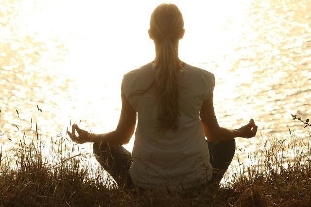光に向かって瞑想している女性の後ろ姿