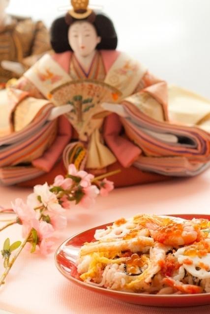 雛人形と桃の花と具がたっぷりのちらし寿司