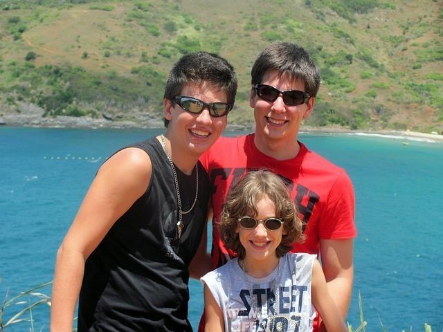 湖をバックにグラサンをかけ年の離れた男の子3人の仲間