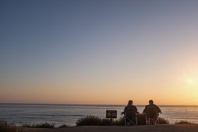 夕暮れの海辺でアウトドアチェアに並んで座っているカップルの後ろ姿