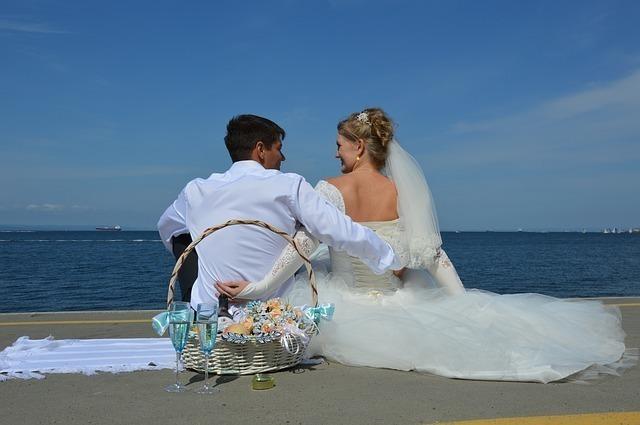 海辺でウエディングドレスを着て男性と座り見つめ合う