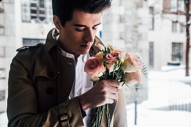ピンクのバラ花を持って香りをかいでいる男性