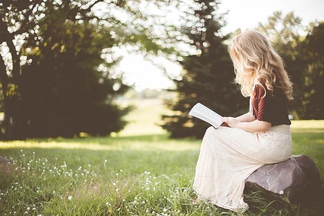 静かな森の前の草原で物語を読む女性の画像