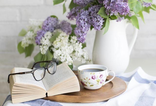花瓶の花の前にあるコーヒーと本と眼鏡の画像