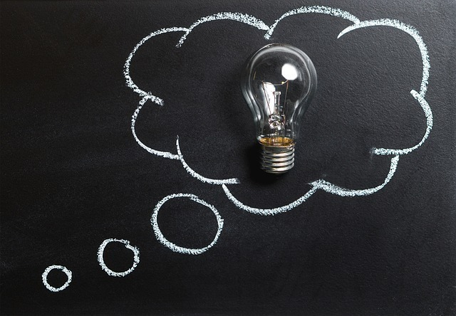 頭の中で考えているふわふわの吹き出しに電球が入っている画像