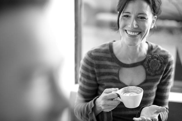 彼の横顔を見つめながらコーヒーを飲んで笑っている女性
