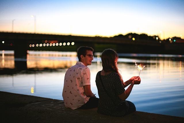 川辺に並んで腰かけて花火を楽しんでいるカップル