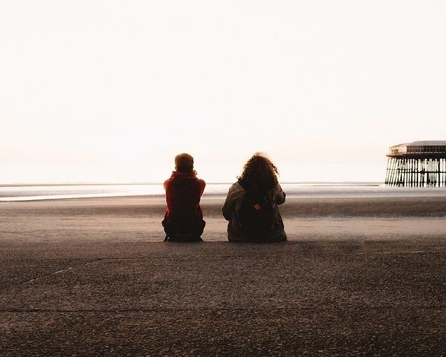 浜辺に並んで腰を下ろして海を見ている二人