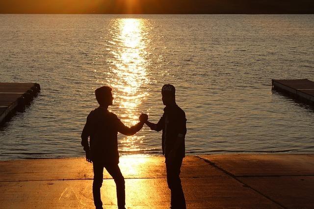 夕暮れの海辺で固い握手を交わす親友同士