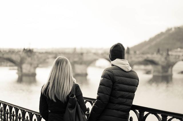 橋の上から並んで川の流れを見つめているカップルの後ろ姿