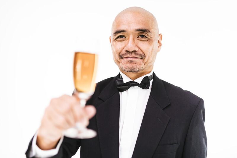 フォーマルスーツでグラスをかかげる坊主頭の男性