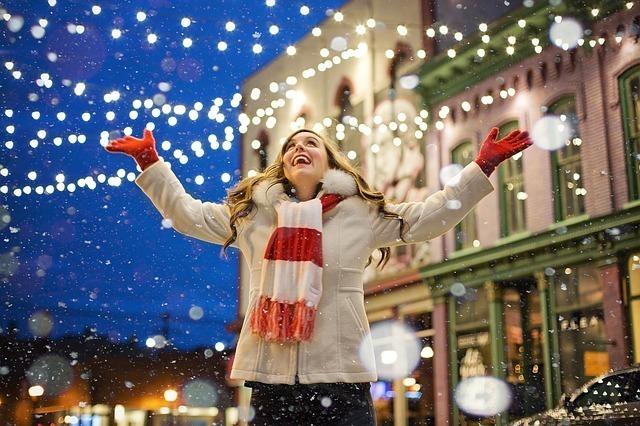 イルミネーションがまぶしい街でホワイトクリスマスを楽しむ女性