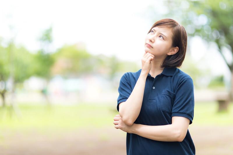 青いポロシャツを着たショートカットの女性が考えるポーズをしている